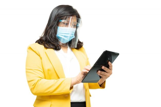 De aziatische bedrijfsvrouwen gebruiken tablet die masker en gezichtsschild op witte achtergrond dragen.