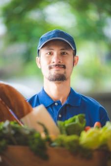 De aziatische bezorger geeft de tas uit de kruidenierswinkel aan de vrouw voor haar huis