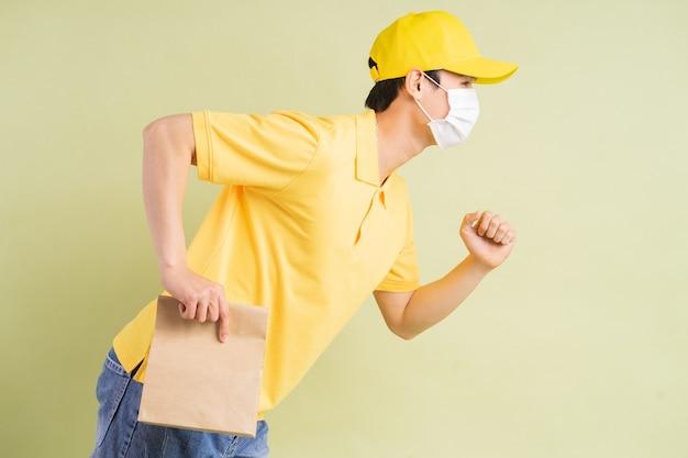 De aziatische bezorger houdt de papieren zak bij zich en rent om de goederen te bezorgen