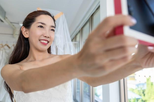 De aziatische dame onderzoekt de spiegel en glimlacht terwijl het kiezen van trouwjurken in winkel.