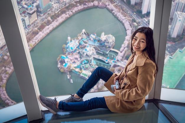 De aziatische dame ontspant op de dak hoogste bar met de stadsachtergrond van seoel