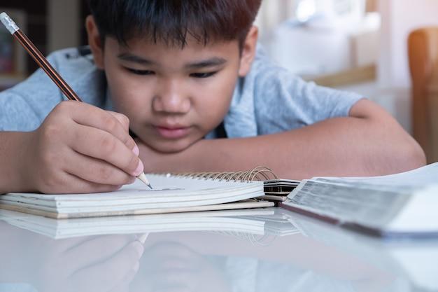 De aziatische elementaire studentjongen legt houdend zijn thuiswerk