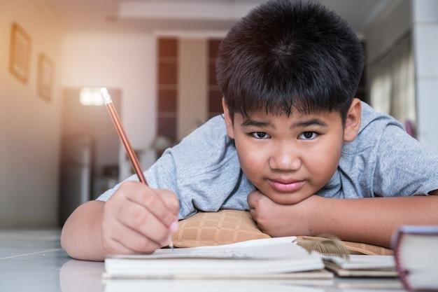 De aziatische elementaire studentjongen legt zijn thuiswerk op notitieboekje terwijl het leren van studie