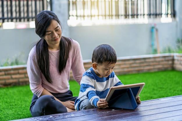 De aziatische familie met zoon kijkt het beeldverhaal via technologietablet en samen speelt wanneer het leven