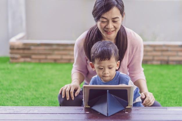 De aziatische familie met zoon kijkt het beeldverhaal via technologietablet en samen speelt