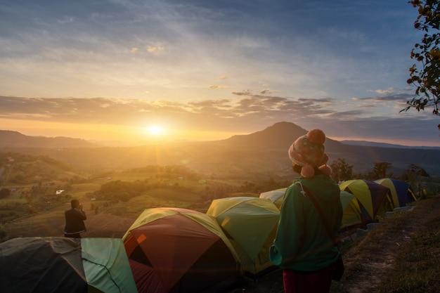 De aziatische gelukkige vrouw en de mening ontspannen tijdens dramatische zonsopgang nevelige ochtend, concept openlucht het kamperen avontuur