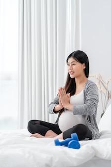 De aziatische gelukkige zwangere vrouw zit en oefent op de bedzwangerschap uit