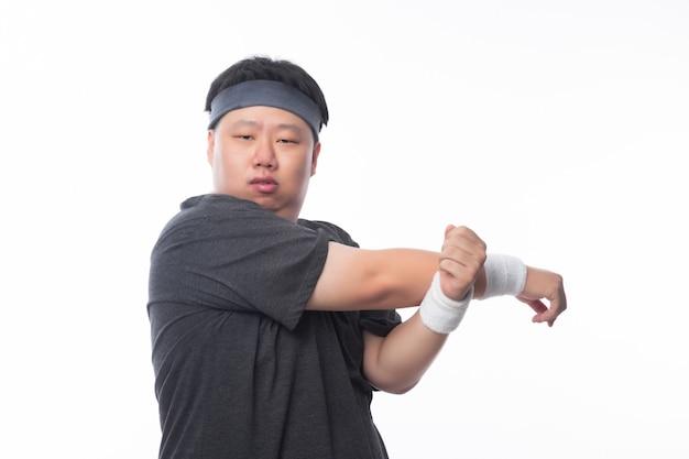 De aziatische grappige vette mens in sportuitrustingen maakt streching vóór training en kijkend aan camera geïsoleerd op witte achtergrond