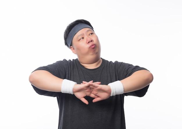 De aziatische grappige vette mens in sportuitrustingen maakt streching vóór training en kijkend aan copyspace geïsoleerd op witte achtergrond