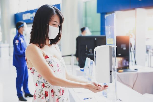 De aziatische handen van de vrouwenwas die automatische ontsmettingsmiddelautomaat gebruiken