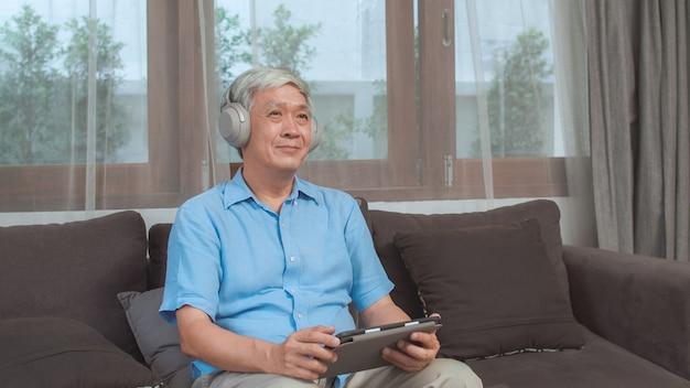 De aziatische hogere mens ontspant thuis. aziatische oudere mannelijke gelukkige slijtagehoofdtelefoon die tablet het luisteren podcast gebruiken terwijl thuis het liggen op bank in woonkamerconcept.