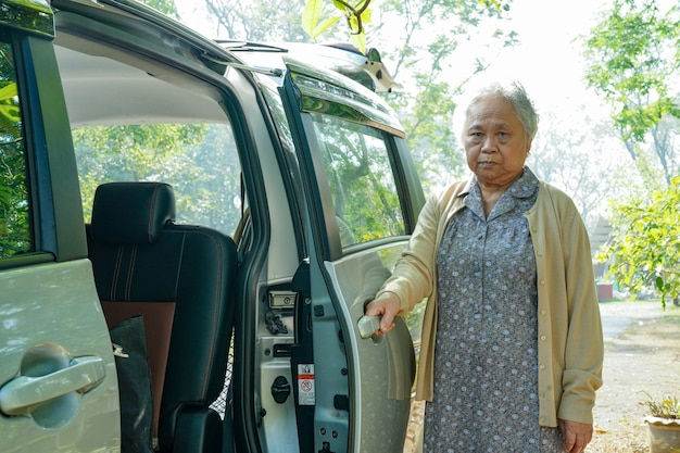 De aziatische hogere of bejaarde oude geduldige zitting van de damevrouw op rolstoel treft voorbereidingen om aan haar auto te krijgen
