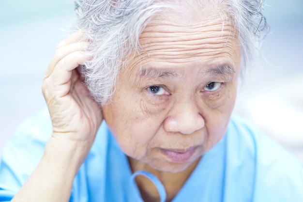 De aziatische hogere of bejaarde oude vrouw van de damevrouw probeert om oor, hard van hoorzitting te luisteren.