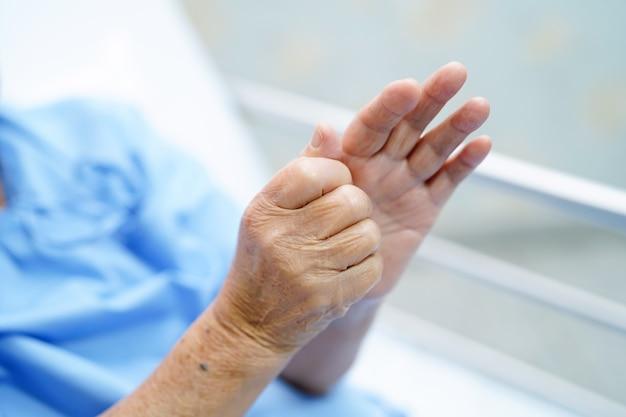 De aziatische hogere of bejaarde oude vrouw van de damevrouw voelt pijn haar hand op bed in de verzorging van het ziekenhuis