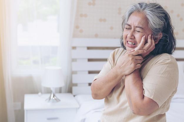 De aziatische hogere tandpijn van vrouwenpatiënten doet pijn - bejaarde medische patiënten en gezondheidszorgconcept
