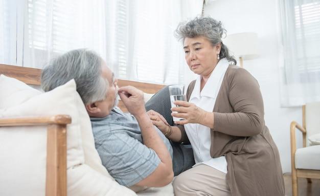 De aziatische hogere vrouw zorgt na geeft glas water aan de oudere man die geneesmiddelen en drinkwater nemen terwijl thuis lig op laag