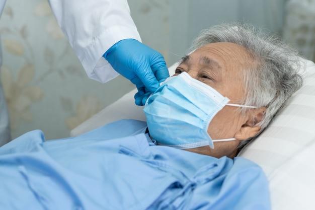 De aziatische hogere vrouwenpatiënt die een gezichtsmasker in het ziekenhuis dragen voor beschermt covid-19 virus.