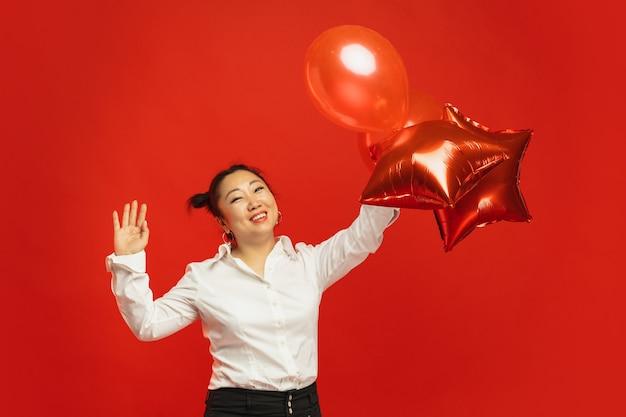 De aziatische jonge ballons van de vrouwenholding op rode muur