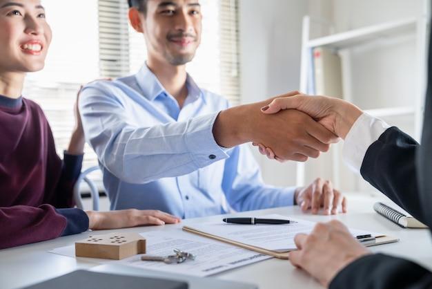 De aziatische jonge handdruk van het familiepaar met makelaar in onroerend goed na gemaakte overeenkomst de lening van het huiscontract van hun