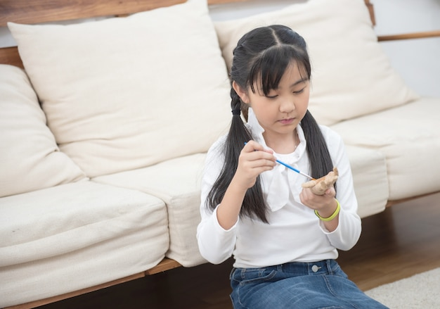 De aziatische jonge houten pop van de meisjesverf thuis