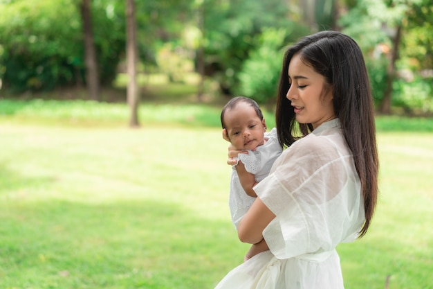De aziatische jonge mooie moeder die haar pasgeboren houdt slaapt en voelt met liefde en raakt zachtjes dan zittend op groen gras in het park