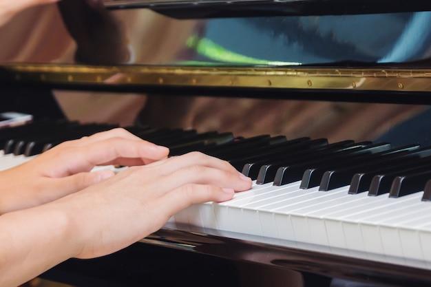 De aziatische jonge piano van de meisjespraktijk thuis