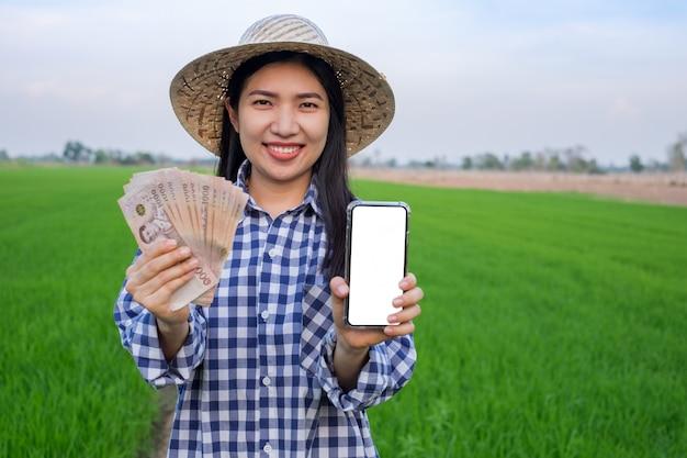 De aziatische jonge tribune van het de glimlachgezicht van de landbouwersvrouw en het houden van het bankbiljetgeld van thailand met het smartphone lege scherm bij groen rijstlandbouwbedrijf. selectieve focus afbeelding