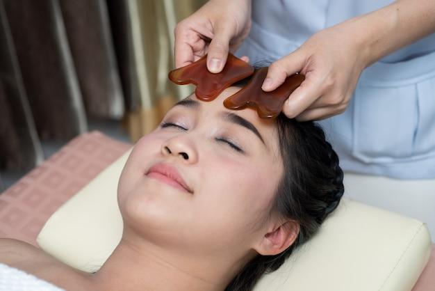 De aziatische jonge vrouw heeft behandeling van gezichtsgasha bij aziatische schoonheidskliniek