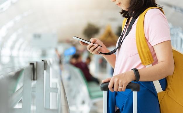 De aziatische jonge vrouw in roze overhemd met gele rugzak controleert vlucht met smartphone op de luchthaven.