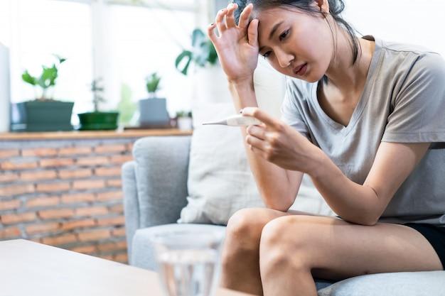 De aziatische jonge vrouw ziek met coronavirus of covid-19 die op hoge temperatuur hebben zit thuis op bank.