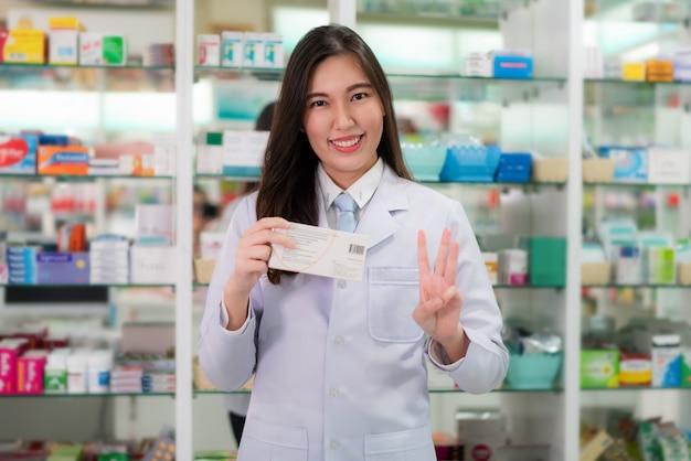 De aziatische jonge vrouwelijke apotheker die vinger drie tonen die aan haar klant verklaren neemt een geneeskunde drie keer of capsule drie per dag.