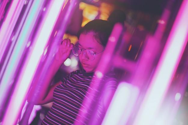 De aziatische jonge vrouwen die glazen dragen bekijken neonlichten die worden verfraaid om op vage bokeh verlichtingsachtergrond te vieren.
