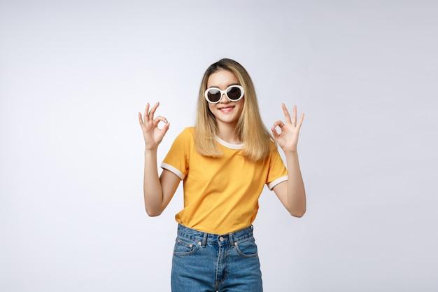 De aziatische jonge vrouwen mooie glimlach met ok vingerteken isoleert op witte achtergrond