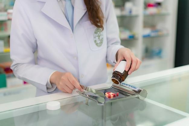 De aziatische jonge vrouwenapotheker giet en telt drugcapsules op roestvrij dienblad, bereidt zij drugspak voor patiënt in de apotheekdrogisterij voor. geneeskunde, farmacie, gezondheidszorg en mensenconcept.