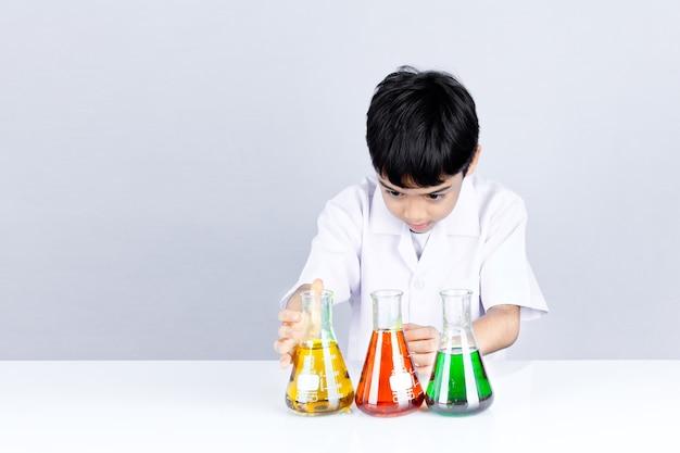 De aziatische jongen bekijkt de combinatie van de testkleur op het onderwijs van het wetenschapsexperiment