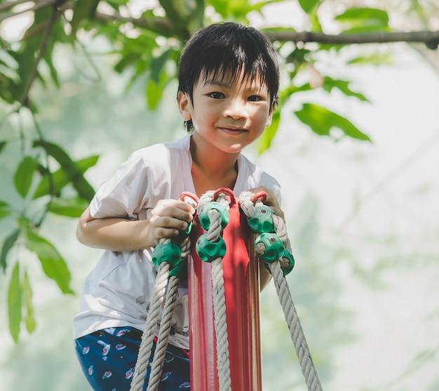 De aziatische jongen beklimt op kabelpool in speelplaats