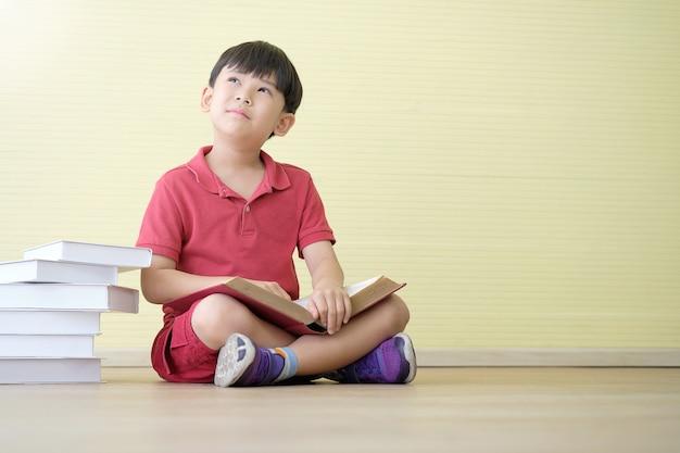De aziatische jongen dagdroomt terwijl het houden van boek en vele boeken die aan kant worden geplaatst.