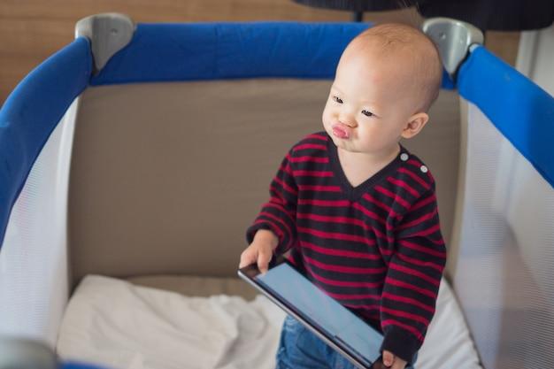 De aziatische jongen die van de peuterbaby zich in voederbak bevinden en tablet houden