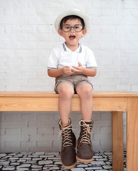 De aziatische jongen draagt bruine laarzen en het glimlachen.