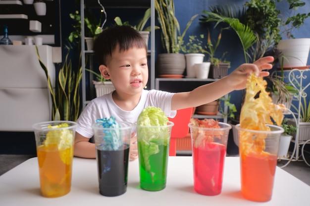 De aziatische jongen heeft pret thuis makend gemakkelijk wetenschappelijk experiment
