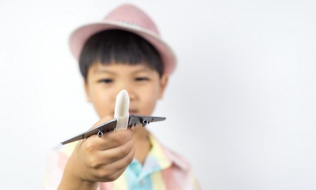 De aziatische jongen houdt een stuk speelgoed vliegtuig met witte exemplaarruimte
