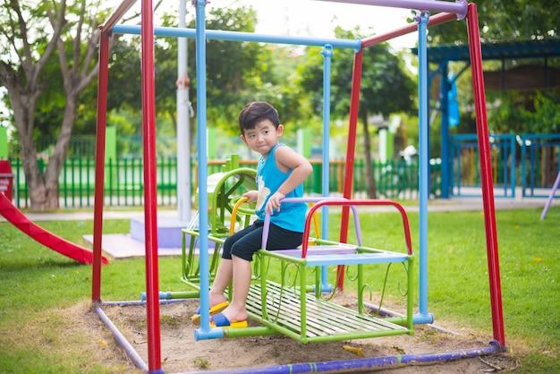 De aziatische jongen speelt een ijzertrein die bij de speelplaats slingert