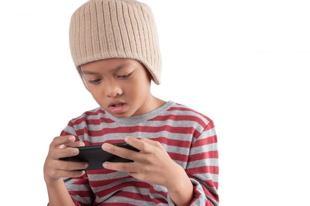 De aziatische jongen speelt spelen op zijn smartphone die op witte achtergrond wordt geïsoleerd.