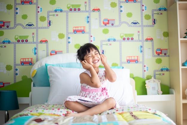 De aziatische kinderen die hoofdtelefoon met behulp van voor luisteren muziek door smartphone op het bed in haar verfraaide slaapkamer