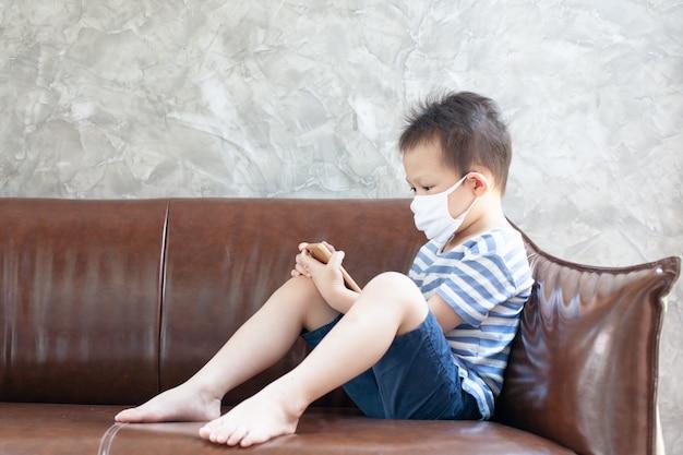 De aziatische kindjongen die beschermingsmasker dragen speelt op de smartphone thuis quarantaine van het coronavirus covid-19 en luchtvervuiling pm2.5.