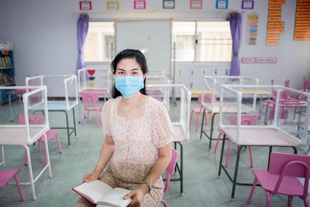 De aziatische leraar draagt een masker in de klas en de school die op het punt staat te beginnen