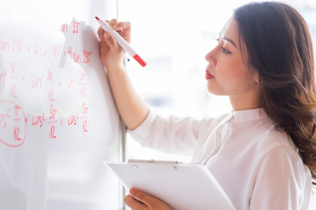 De aziatische lerares herschrijft de lezing op het bord