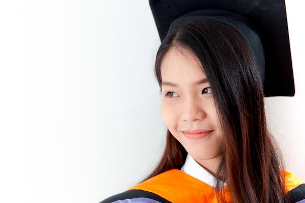 De aziatische leuke die graduatie van het vrouwenportret op wit, de universiteit van thailand wordt geïsoleerd.