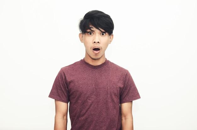 De aziatische man glimlachte in een casual shirt met een geschokte uitdrukking