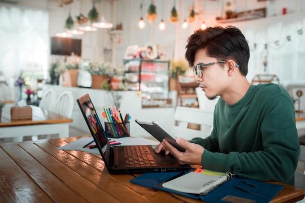 De aziatische mannelijke student werkt gebruikend een laptop zitting bij een houten lijst in een koffiewinkel